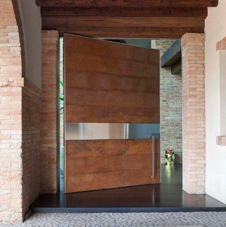 puerta pivotante en madera de framire con detalle en acero